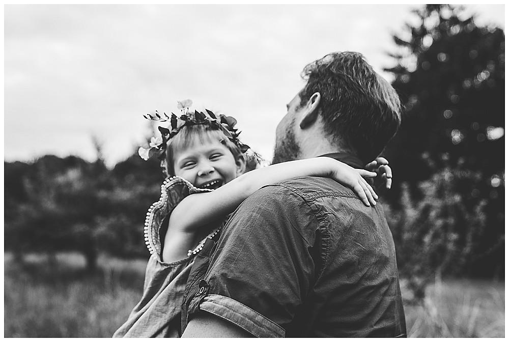 kind lacht und umarmt Papa