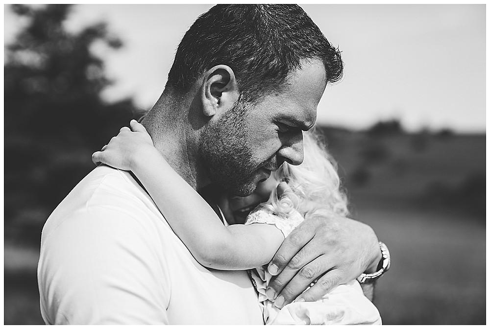Papa umarmt Tochter und trägt sie
