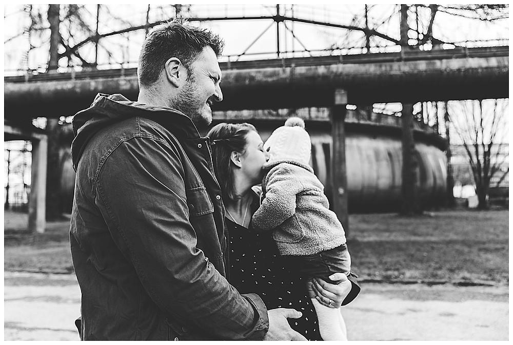 Papa hält Schwangerschaftsbauch mama küsst große Schwester