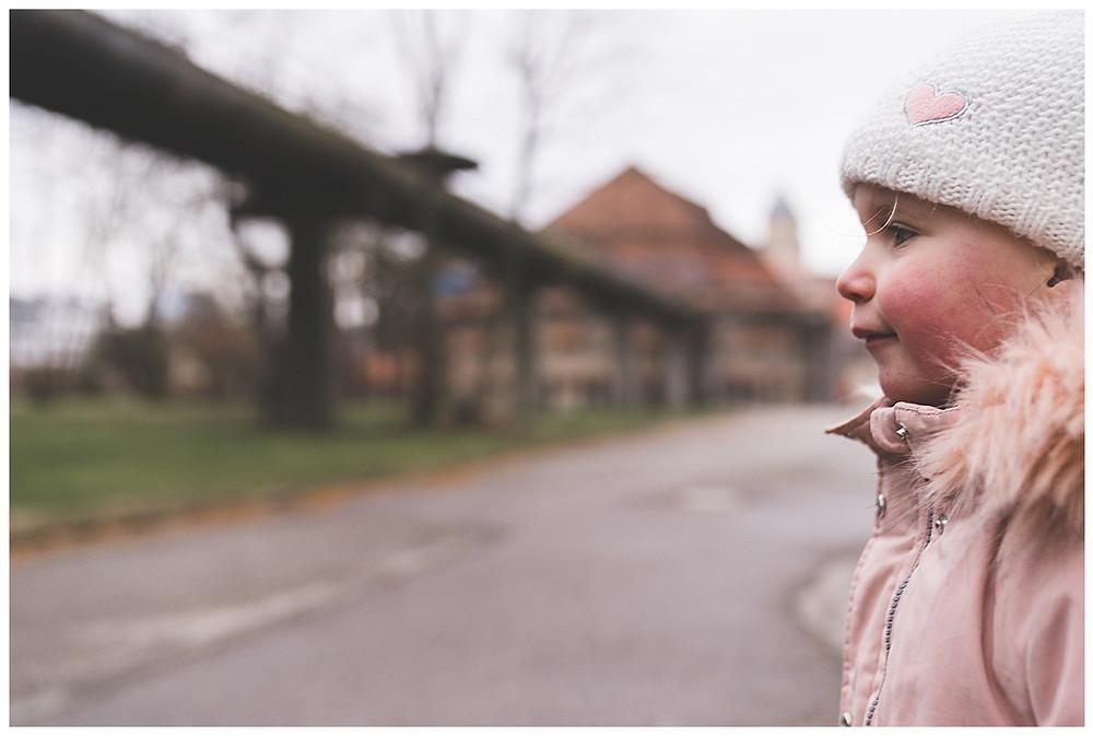 Kind mit Mütze läuft weg beim Familienshoot in Augsburg im Gaswerk