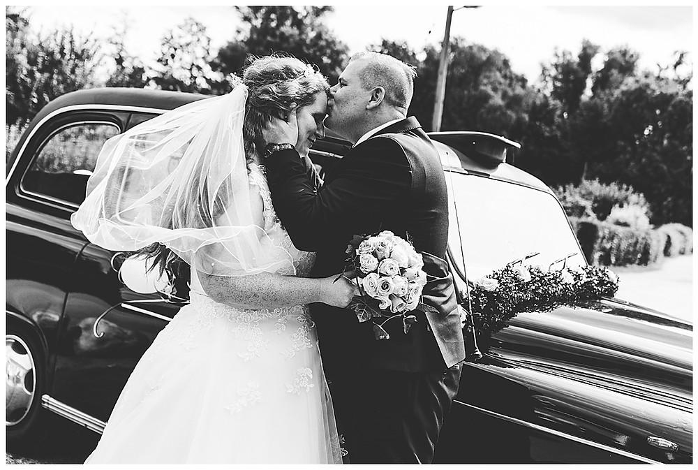 Bräutigam küsst Braut auf die Stirn Oldtimer im Hintergrund mit wehendem Schleier in Hamburg