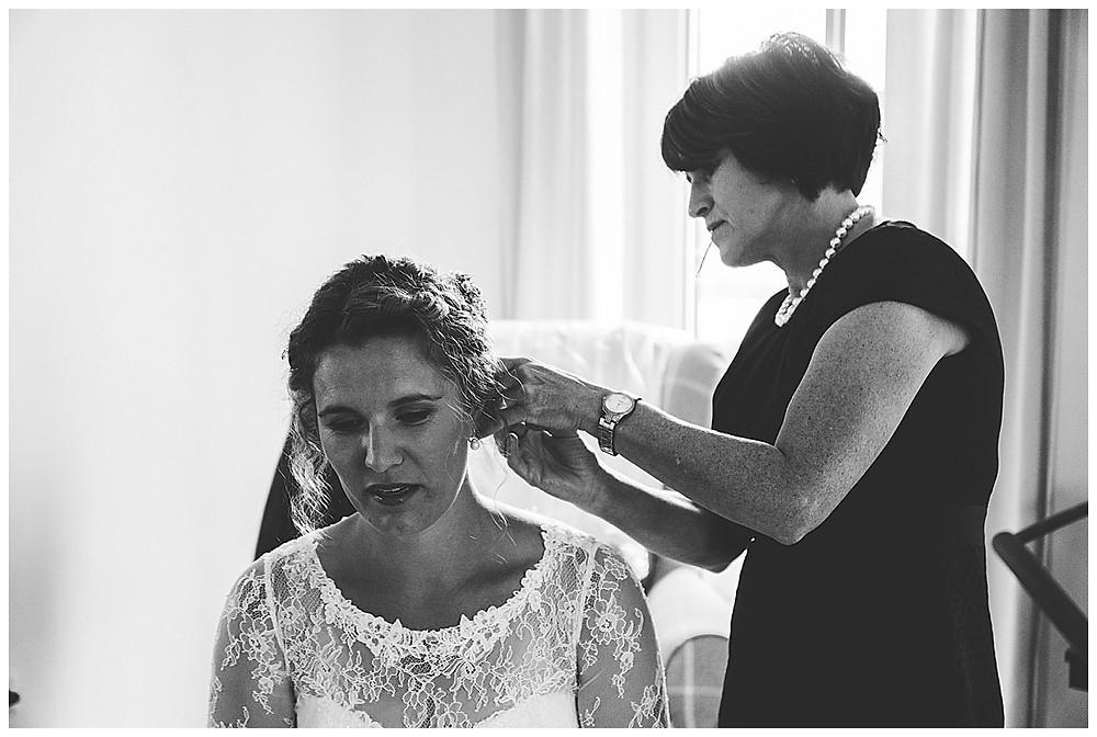 Brautmutter richtet Haare von Braut