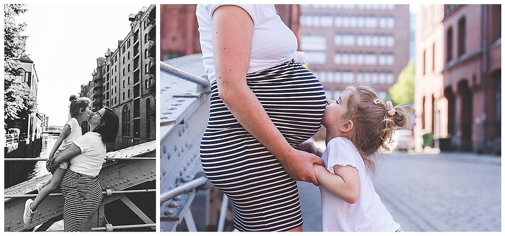 Kind küsst schwangere Mama in der Hamburger Speicherstadt