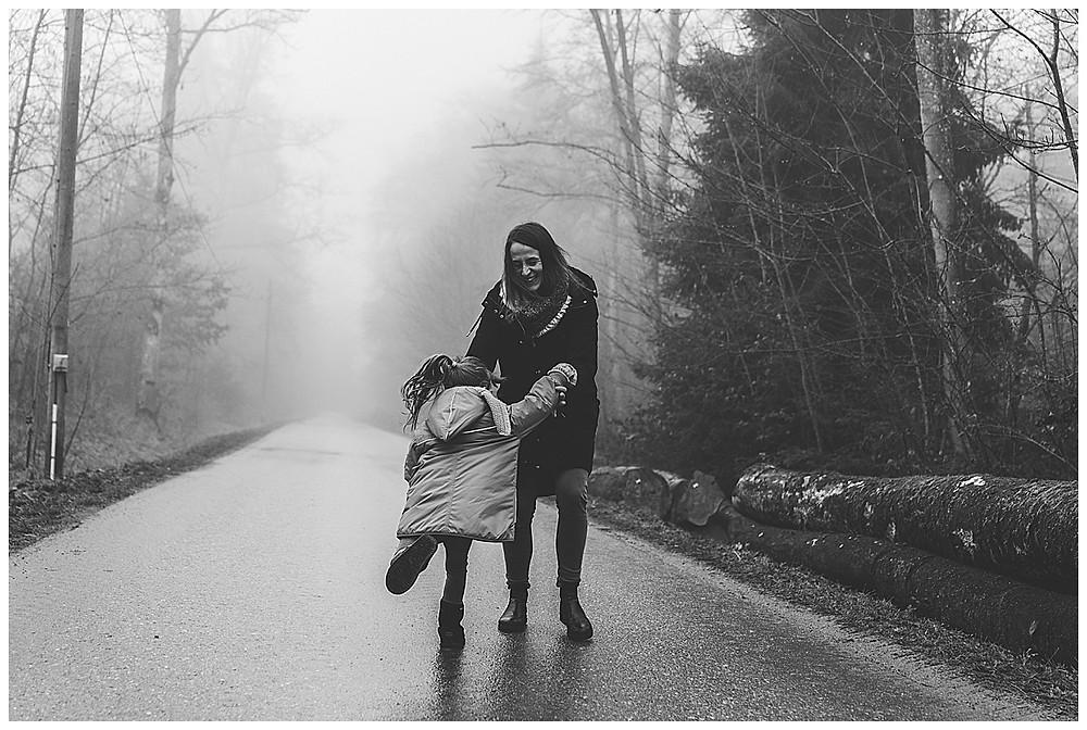 mama und kind toben im Nebel