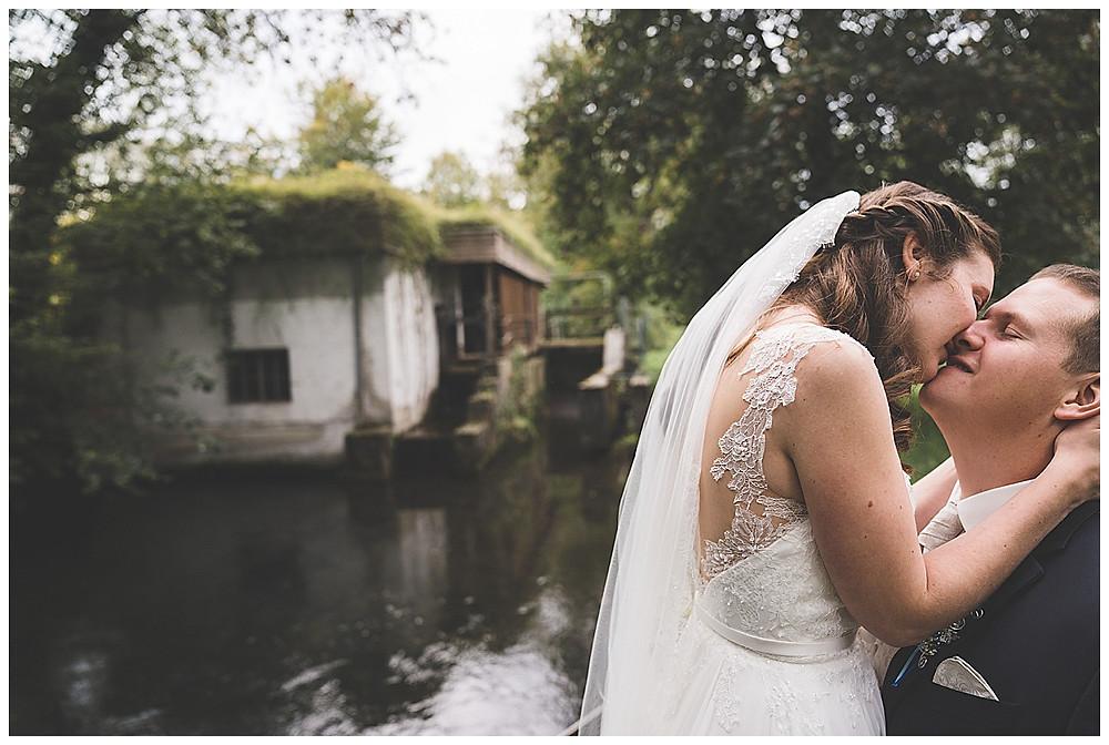 Brautpaar küsst sich am Wasser