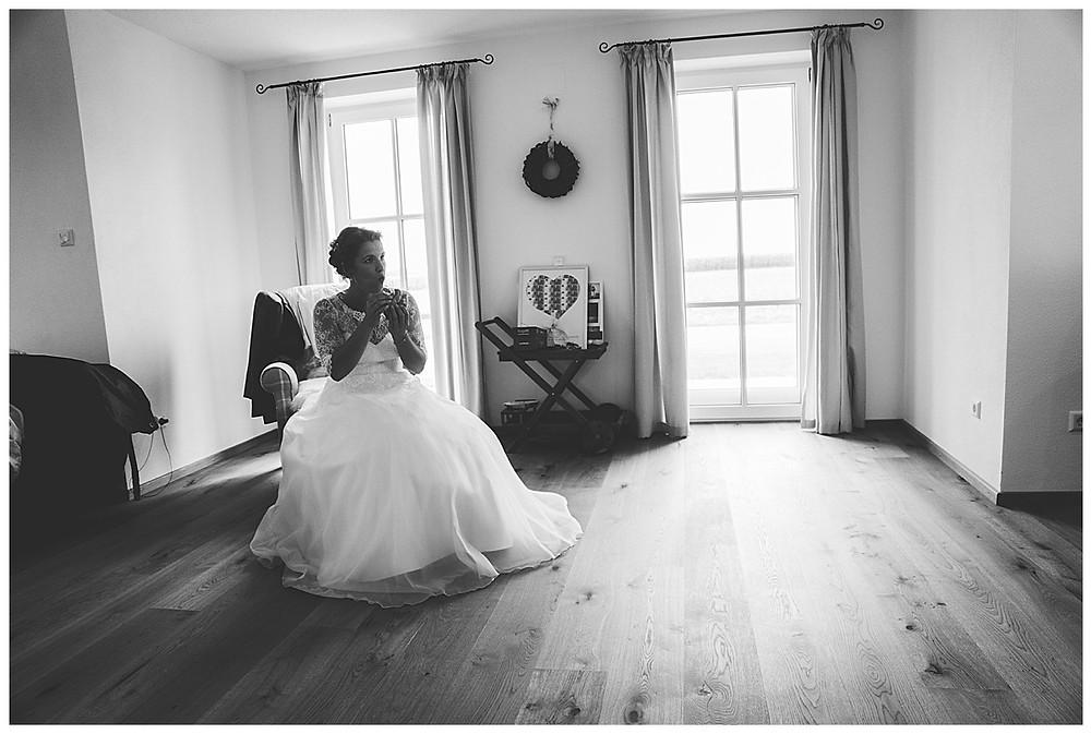 Braut sitzt zuhause im Kleid und isst