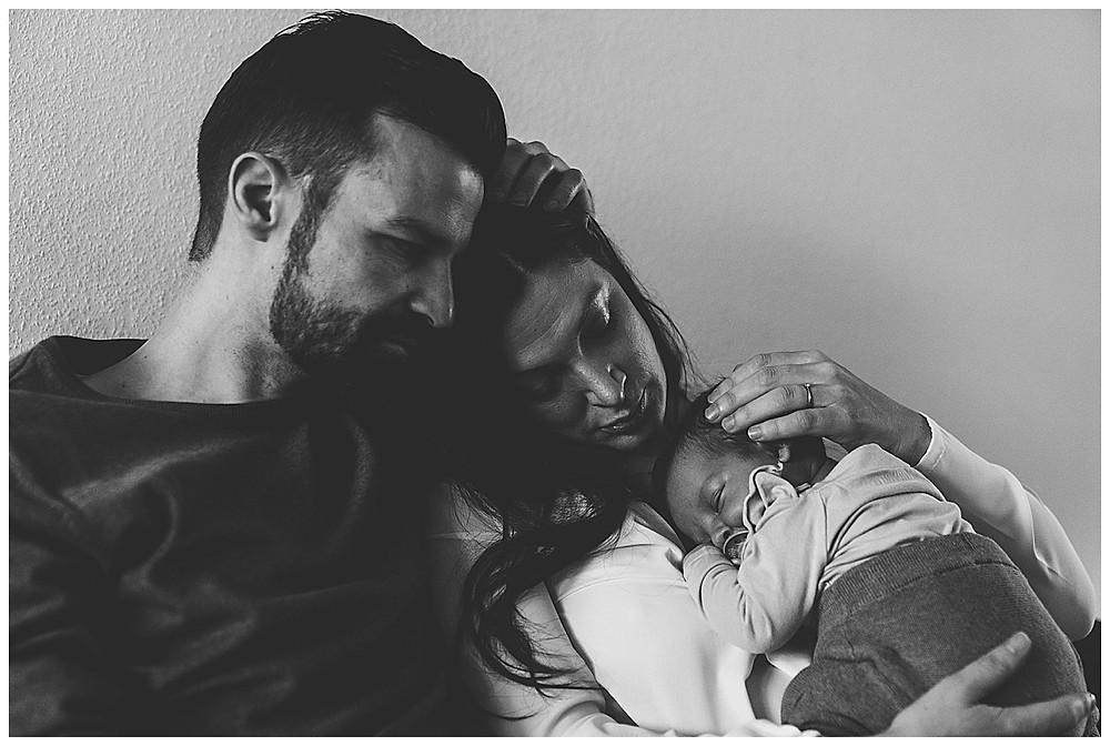 Eltern kuscheln mit Baby bei Familienshooting zuhause