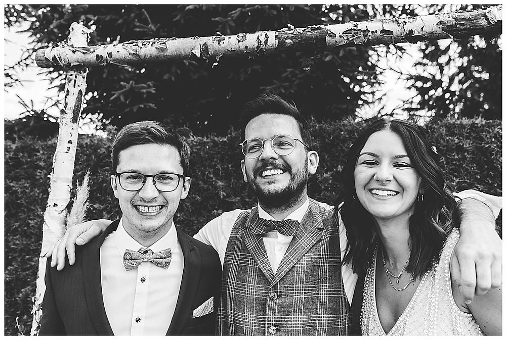Bräutigam umarmt Bruder und Schwester