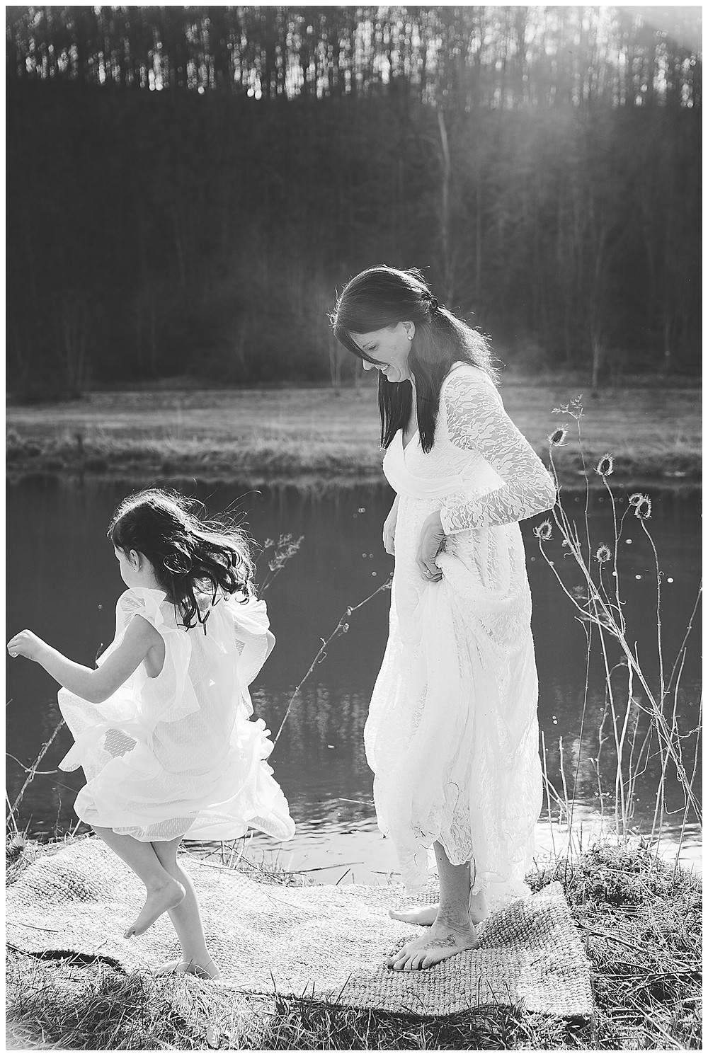 Mama tanzt am Wasser mit Kind bei Sonnenschein