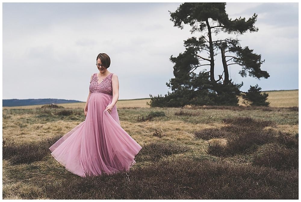 schwangere Frau im Kleid freut sich bei Babybauchshooting