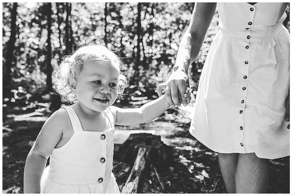 Kind läuft an Hand von Mama