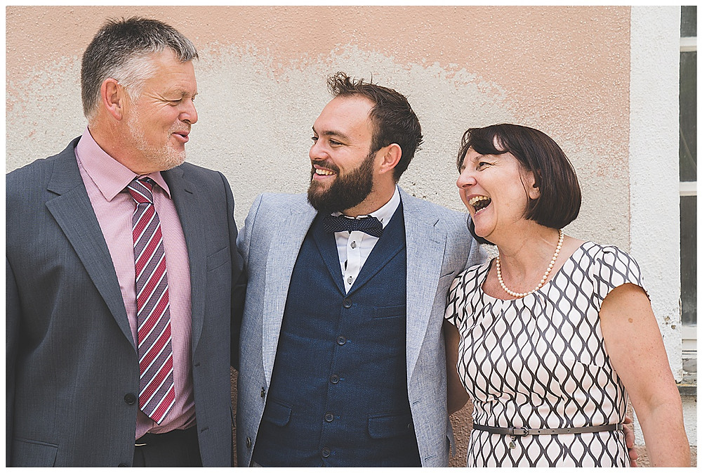 Bräutigameltern lachen mit Sohn