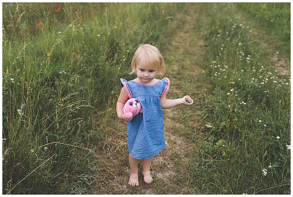 Kind steht auf Feldweg  mit kuscheltier in der Hand