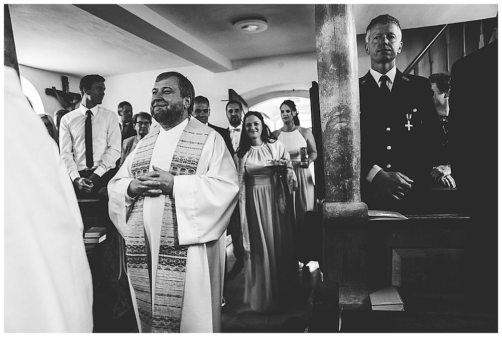 Brautpaar zeiht mit Pfarrer in die Kirche ein
