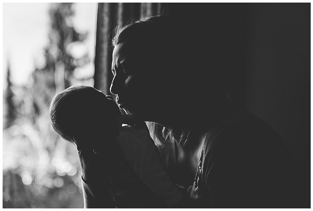 mama küsst ihr Baby am Fenster