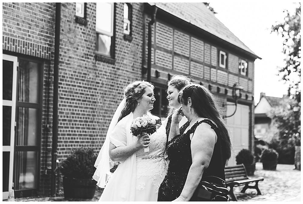 Braut steht mit Mama und Schwester am Rathaus in Ammersbek