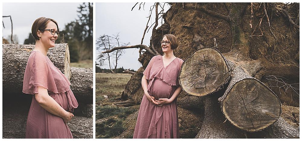 schwangere Frau hebt ihren Babybauch und lehnt an Baumwurzel