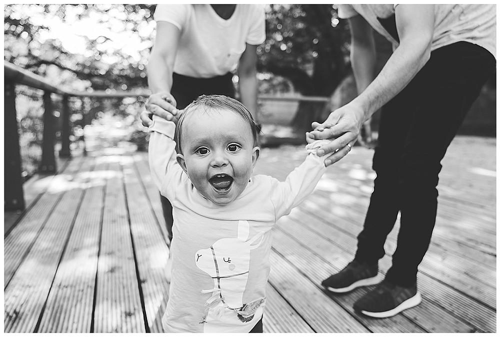 lachendes Kind im Park an der Hand der Eltern