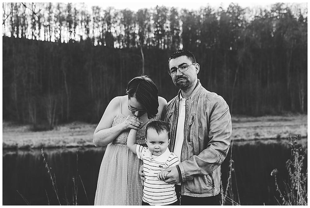 Schwangere Mama küsst Hand von Sohn Papa schaut zu