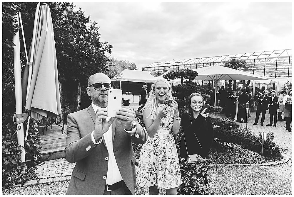 Gäste machen Fotos vom Brautpaar