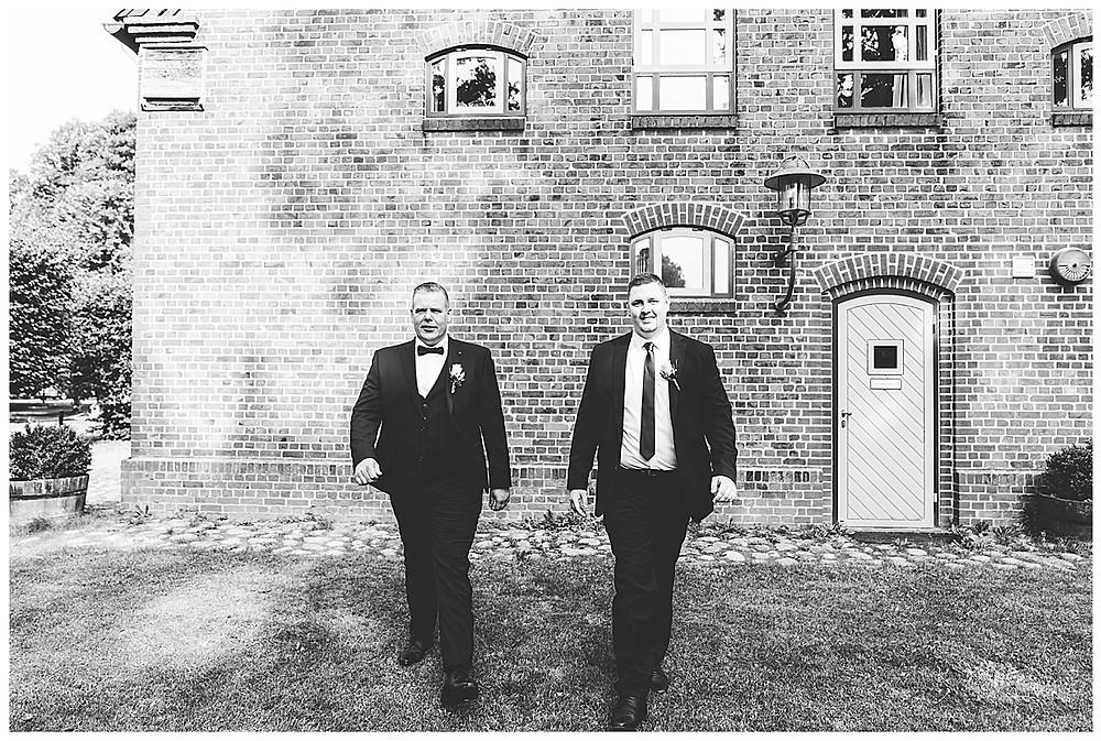 Bräutigam und Trauzeuge laufen auf Fotograf in Ammersbek zu