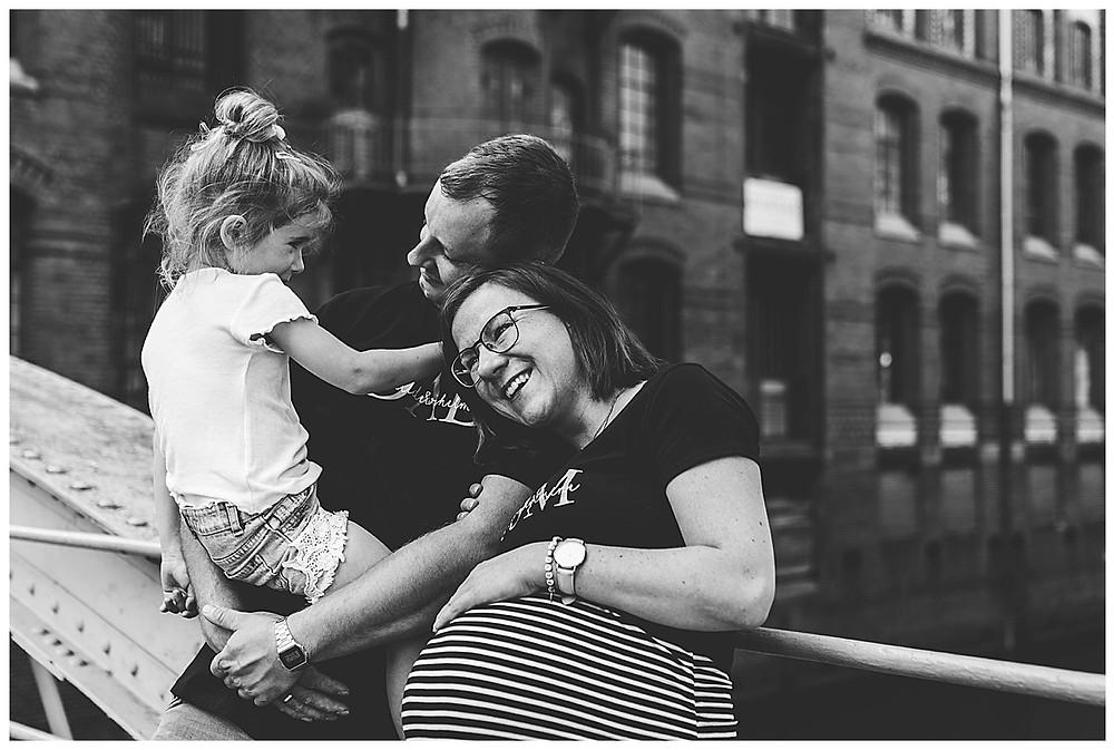 Babybauchfotografie Hamburg Kind kuschelt mit Eltern Mama hält Bauch
