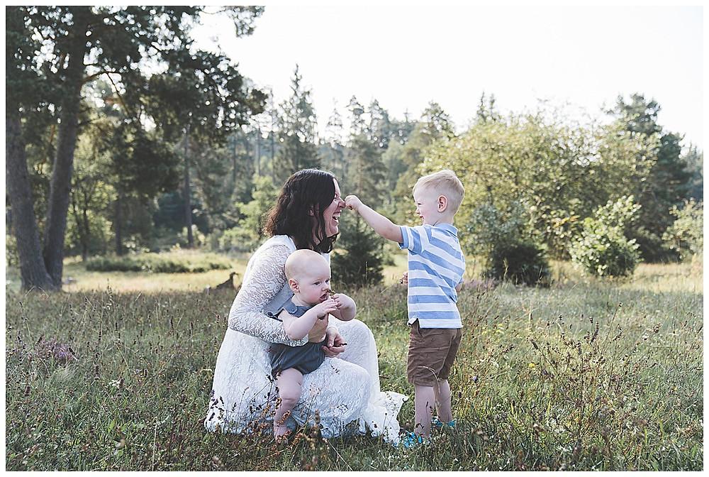 mama und ihre zwei Söhne beim Fotoshooting in der Natur