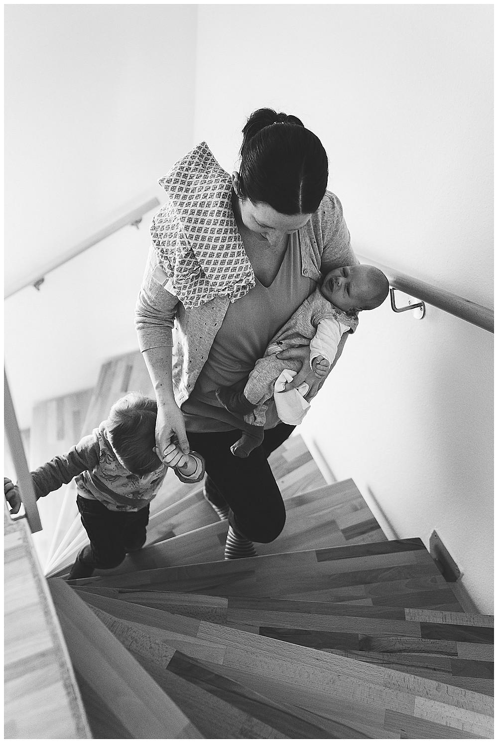 Mama und ihre zwei Kinder gehen Treppe hoch
