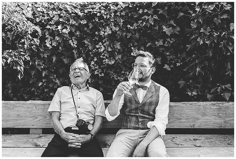 Bräutigam und Opa sitzen auf Bank