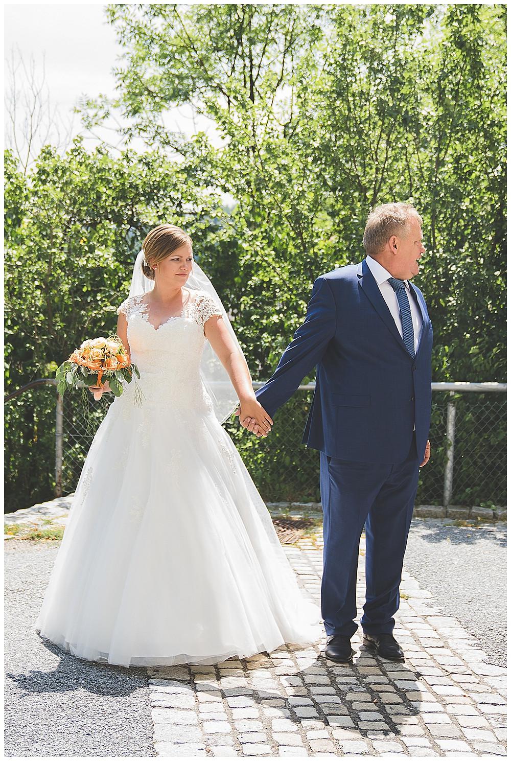 Braut und Papa vor Kirche Hand in Hand