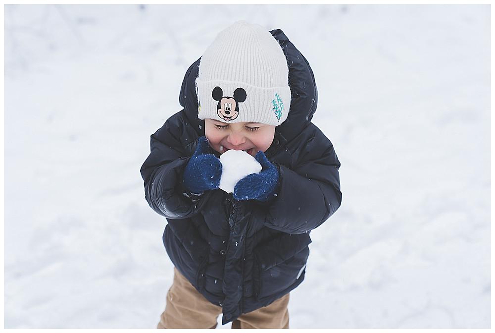 Kind isst Schnee im Winter