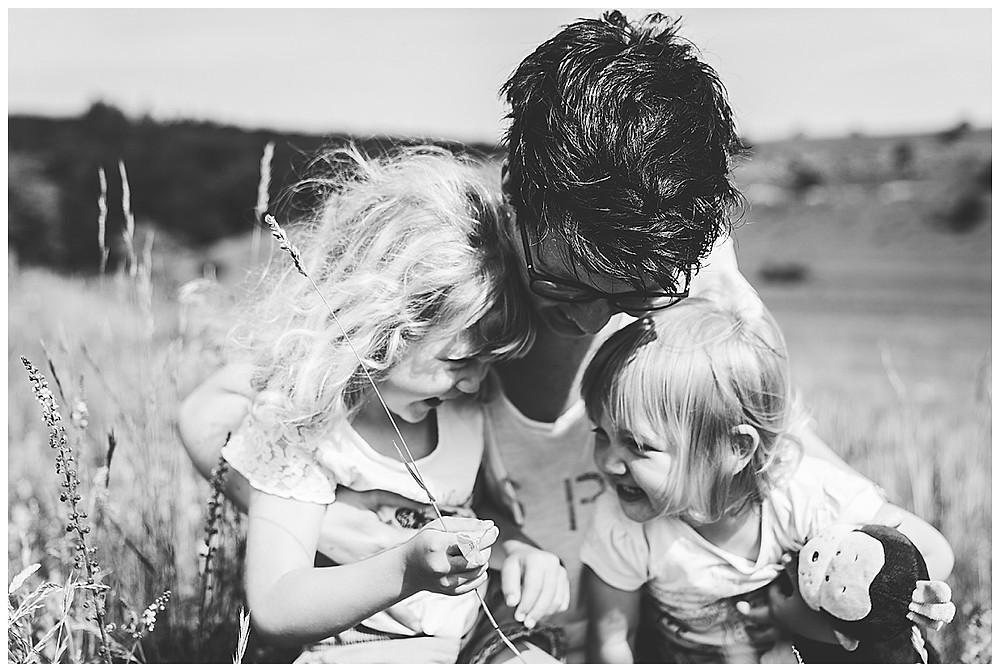 Mama und ihre Töchter lachen beim Blumenpflücken