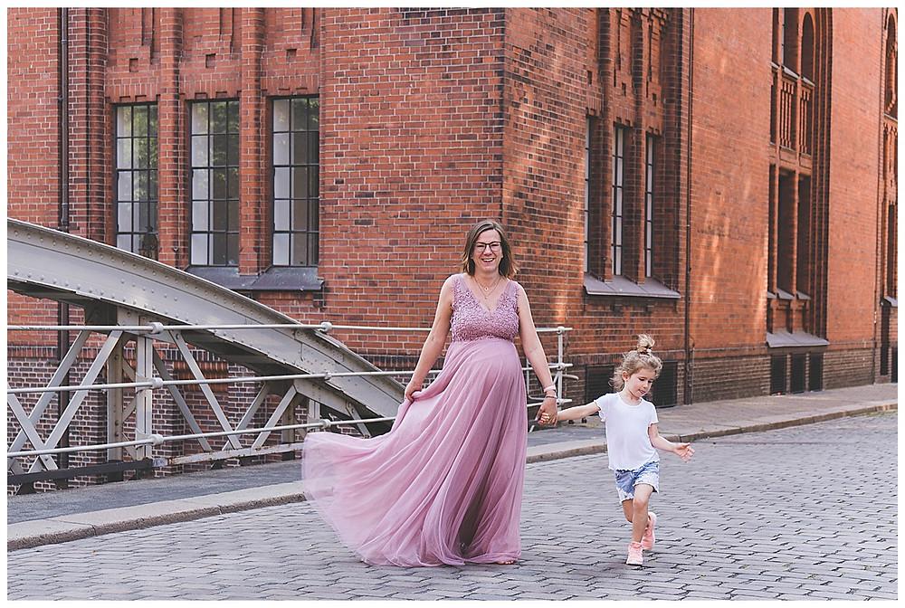 schwangere in Kleid in Speicherstadt Fotoshooting Hamburg  und Geschwisterkind an der Hand