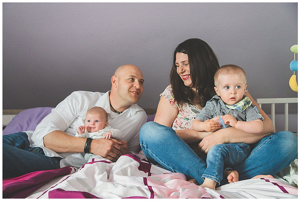 Babyfotografie in Augsburg Eltern und Söhne im Schlafzimmer lachend