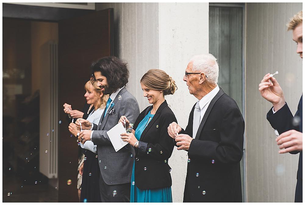 Gäste warten auf Brautpaar vor Kirche