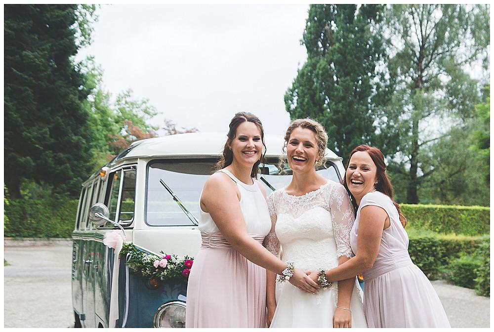 Braut und Trauzeuginnen lachend vor VW Bulli