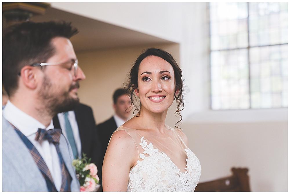 Braut lächelt ihn an in Kirche