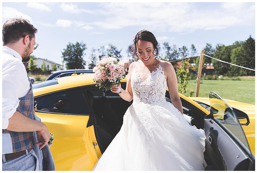 Braut steigt aus gelben Mustang
