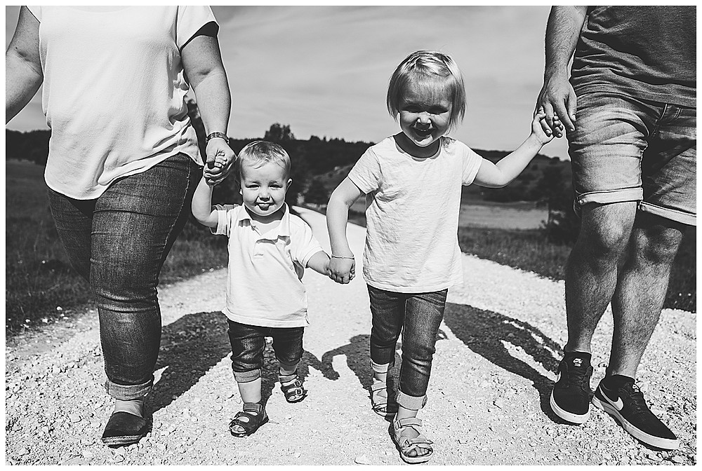 mama papa und ihre zwei Kinder laufen spazieren Hand in Hand