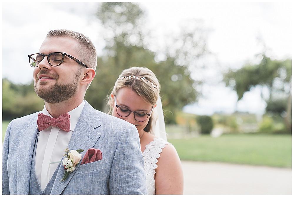 Braut steht hinter Bräutigam