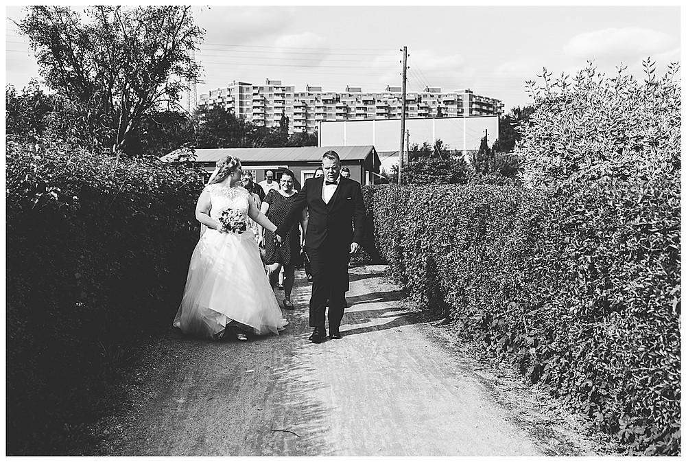 Brautpaar und Gäste laufen in Hamburg Kleingartenanlage