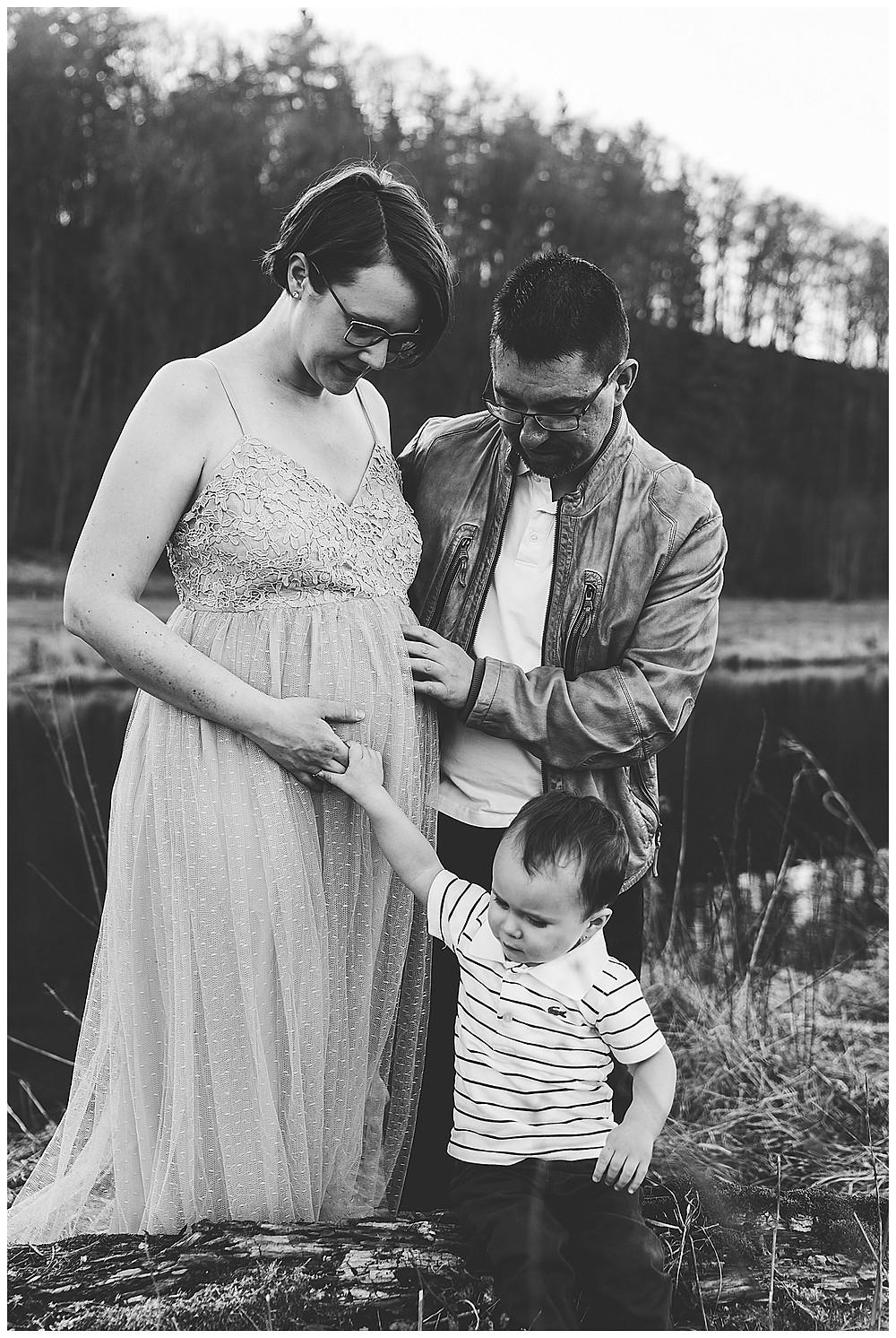 Geschwisterkind langt an Mamas Babybauch Papa hält die Hand