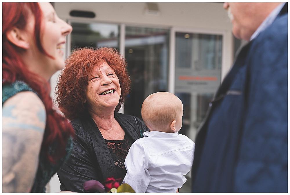 Brautmama mit Enkel auf Arm lacht