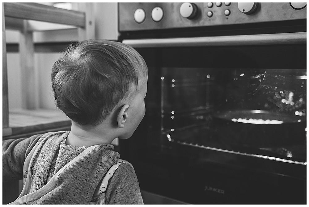Kind schaut in Backofen