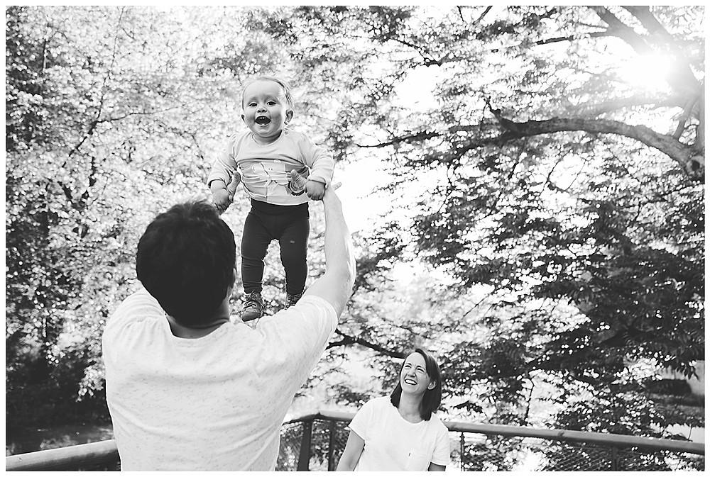 Papa wirft Kind hoch und lacht im Park