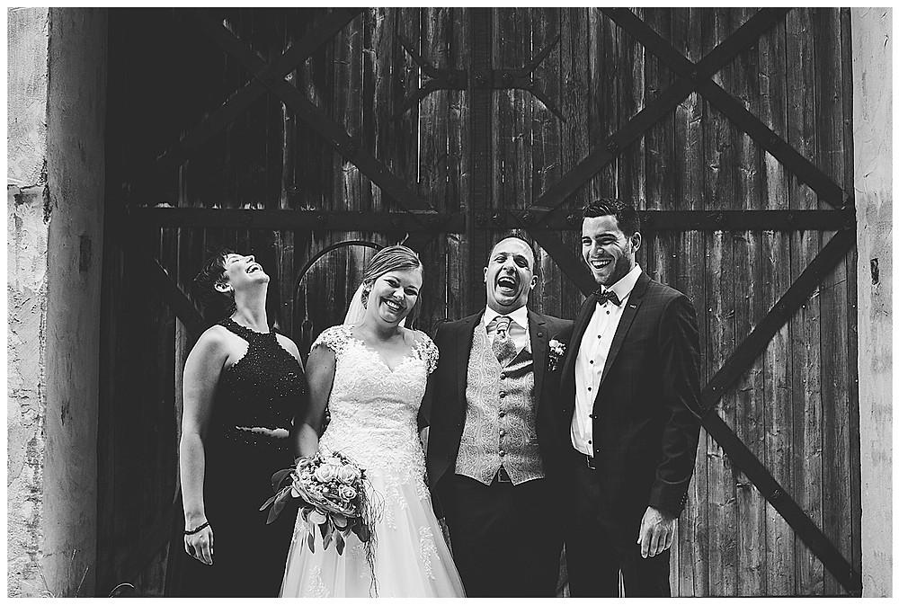 Brautpaar und Trauzeugen lachen laut und herzhaft