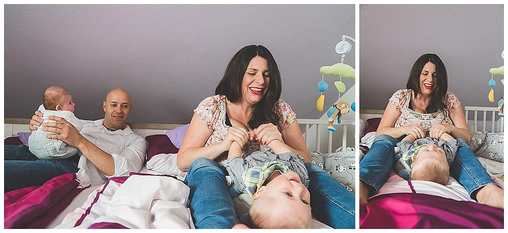 Babyfotografie in Augsburg Eltern und Söhne im Schlafzimmer tobend