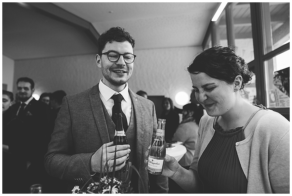 Gäste trinken Bier an Hochzeit und lachen