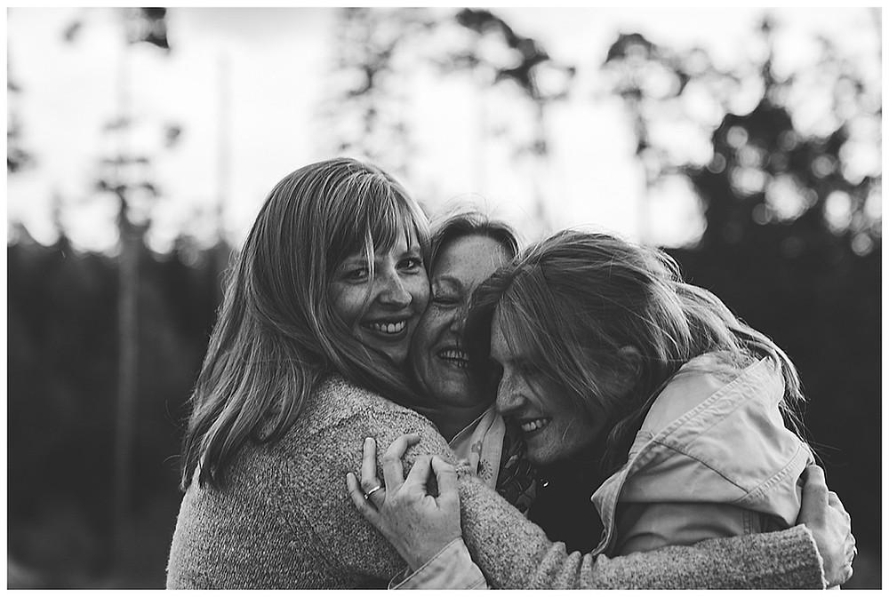 Mama wird von Töchtern umarmt