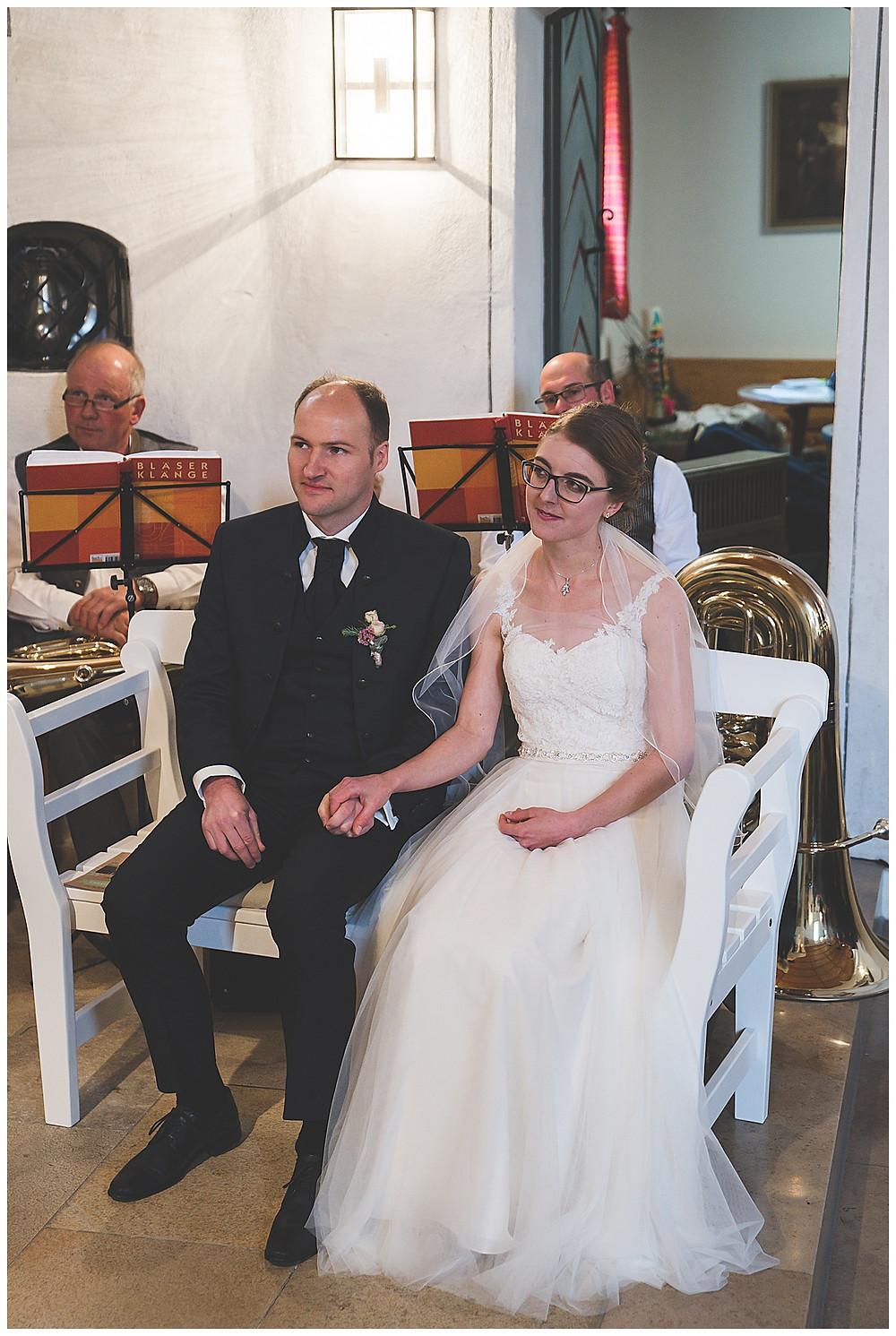 Brautpaar hält Händchen in Kirche